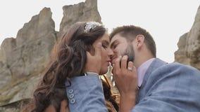Bruidegom met bruid dichtbij bergheuvels Het paar van het huwelijk in liefde sunbeams stock video