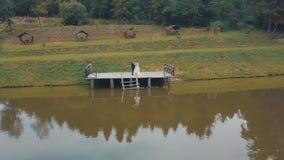 Bruidegom met bruid dichtbij meer in het park Het Paar van het huwelijk Luchtschot royalty-vrije stock fotografie
