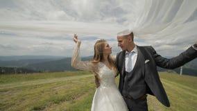 Bruidegom met bruid die pret op een bergheuvels hebben Huwelijkspaar onder de sluier Gelukkige Familie Man en vrouw in liefde Moo stock video