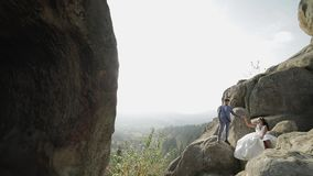 Bruidegom met bruid op een hoge helling van de berg Het Paar van het huwelijk sunbeams stock footage