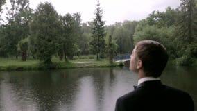 Bruidegom met een boeket dichtbij het meer stock videobeelden