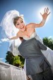 Bruidegom opheffende bruid op schouder en het vervoeren van haar Royalty-vrije Stock Afbeeldingen