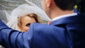 Bruidegom opheffende sluier van het richten van bruidengezicht stock footage