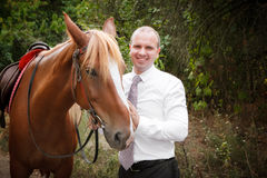 Bruidegom tijdens gang in hun huwelijksdag tegen een bruin paard royalty-vrije stock afbeeldingen