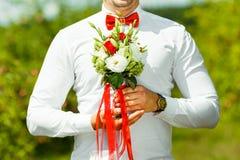 Bruidegomholding in boeket van het handen het gevoelige, dure, in bruids huwelijk van bloemen in rood en wit Stock Afbeelding