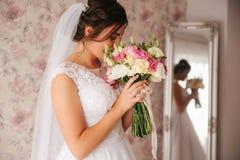 Bruidgreep een boeket van bloemen in haar hand De dag van het huwelijk stock afbeeldingen