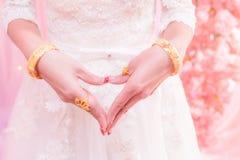 Bruidhanden als een hart met gouden trouwring & armbanden worden gevormd die Royalty-vrije Stock Foto