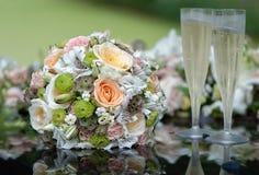 Bruids boeket en champagneglazen op de bonnet van de huwelijksauto stock afbeeldingen