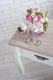 bruids boeket met trouwringen en wijnglazen op de lijst in de ochtend van de dag stock fotografie