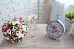 bruids boeket met trouwringen en wijnglazen op de lijst in de ochtend van de dag, mooie uitstekende horloges stock afbeelding
