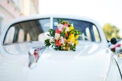 Bruids boeket op de kap van het retro voertuig Stock Afbeeldingen