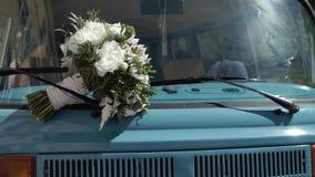 Bruids boeket op een kap van blauwe retro bus stock video