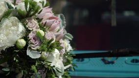 Bruids boeket op een kap van blauwe retro bus stock videobeelden