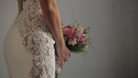 Bruids Mooi boeket in handen van bruid, witte huwelijkskleding stock videobeelden