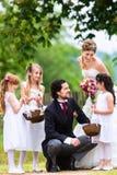 Bruids paar bij huwelijk met bruidsmeisjekinderen royalty-vrije stock foto's
