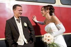 Bruids paar dat op wagen wordt geleund Stock Foto's