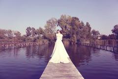 Bruids paar op houten brug bij meer Royalty-vrije Stock Fotografie