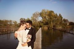 Bruids paar op houten brug bij meer Royalty-vrije Stock Afbeelding