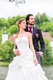 Bruids paar in park, de bruid van de bruidegomholding Royalty-vrije Stock Foto's