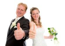 Bruids paar voor witte achtergrond met omhoog duim Stock Foto's