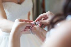 Bruids voorbereiding, bruid die op juwelen, nadruk op armband zetten Stock Afbeelding