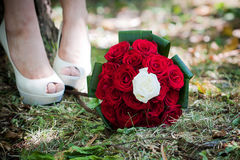 Bruidschoenen met huwelijksboeket stock afbeelding
