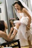 Bruidsmeisje dat kouseband plaatst. Royalty-vrije Stock Foto's