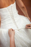 Bruidsmeisje die de bruid helpen om haar kleding te zetten Royalty-vrije Stock Foto's