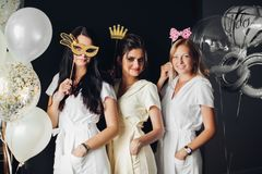 Bruidsmeisje die grappige maskers dragen die met vlecht stellen royalty-vrije stock foto