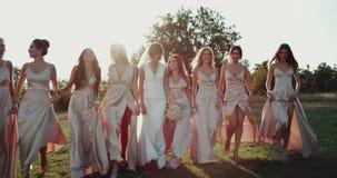 Bruidsmeisje en bruid het mooie lopen op het gras met verbazende zonsondergangachtergrond Rood Heldendicht 4K stock video