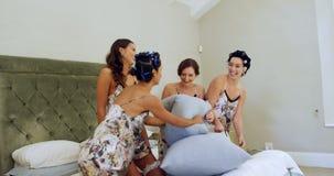 Bruidsmeisjes die in nachtjapon van hoofdkussen de genieten bestrijden 4K 4k stock videobeelden