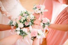 Bruidsmeisjesbruidsmeisjes van bloemen op hun handen stock foto's