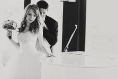 Bruidtribunes nadenkend achter een piano terwijl de bruidegom haar van koestert Royalty-vrije Stock Afbeeldingen