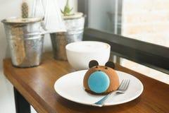 Bruin draag cake met blauwe macaronneus met kop van koffie op houten lijst bij koffie Vaag installaties en venster op achtergrond Royalty-vrije Stock Foto