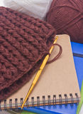 Bruin haak hoed met gouden haak, garens en boeken. Stock Fotografie