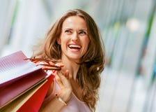 Bruin-haired, gelukkige, glimlachende vrouw die het winkelen zakken steunen stock fotografie