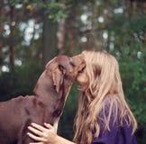 Bruin hoor meisje het kussen hond Stock Foto