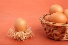 Bruin kippenei in het meest strawnest en eieren in de mand Stock Foto's