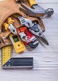Bruin leer toolbelt met bouwhulpmiddelen op houten raad dir Stock Foto
