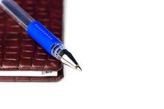 Bruin leernotitieboekje met blauwe die pen op wit met selectieve nadruk en vrije ruimte wordt geïsoleerd royalty-vrije stock afbeeldingen