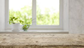 Bruin oud houten tafelblad met vaag venster voor productvertoning stock afbeelding