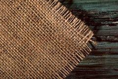 Bruin servet op de linkerzijde van de jute op een houten achtergrond stock afbeelding