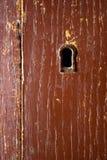 Bruin sleutelgat op houten poort Stock Foto's