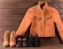 Bruin suèdejasje en drie verschillende paren schoenen op houten Stock Afbeelding