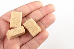 Bruin Sugar Cubes In The Hand boven Witte Achtergrond royalty-vrije stock foto's