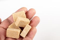Bruin Sugar Cubes In The Hand boven Witte Achtergrond stock foto