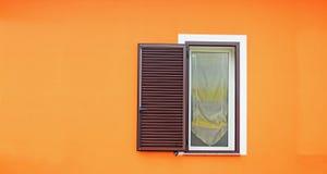 Bruin venster in een oranje muur royalty-vrije stock fotografie