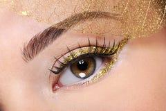 Bruin vrouwelijk oog met een aantrekkingskracht gouden samenstelling Royalty-vrije Stock Foto