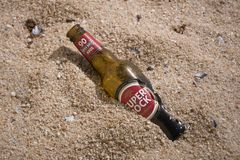Bruine bierfles Portugees bier op het strand stock foto