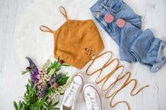 Bruine bovenkant met banden, jeans, witte tennisschoenen Boeket van wildernis Royalty-vrije Stock Foto
